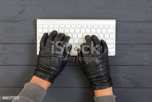 istock Hacker Hands breaking network protection on wood background 840177222