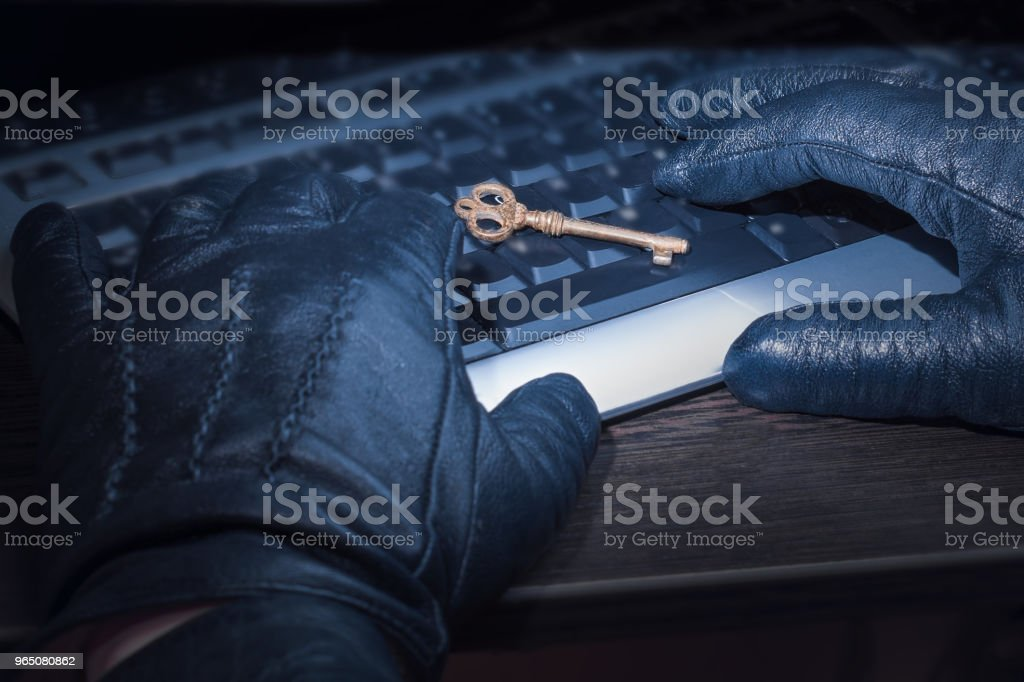 Hacker hands working on a laptop computer having an access key. The concept of hacking business strategy and social networks zbiór zdjęć royalty-free