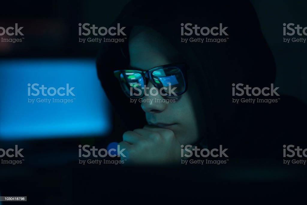 Hacker hiding in the dark and working with computers stock photo