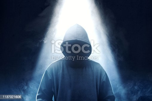 Hacker in black hoodie standing with smoke and light from the top over dark background
