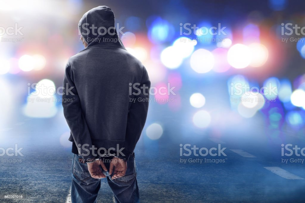 Hacker in handcuffs stock photo