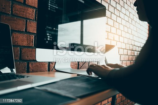 istock Hacker in the hood working with computer with hacking breaking into data servers. 1172847252