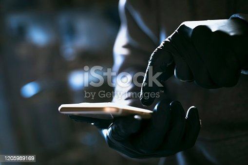 hacker in the hood working with mobile phone typing text in dark room