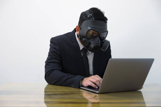 Hacker man in suit and toxic mask stock photo