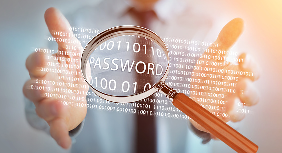 istock Hacker on blurred background using digital magnifying glass to find password 3D rendering 1211202854