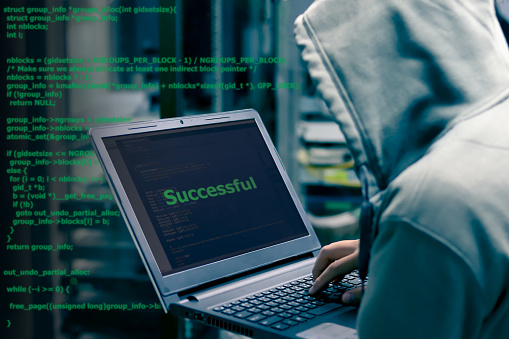 istock Hacker Organizes Massive Data Breach Attack on Corporate Servers with code programming in background. He is in  Secret Location. Their Hideout is Dark, Neon Lit 1035299508
