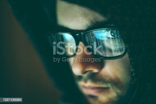 Close up of male hacker's face looking to the camera through eyeglasses covered with binary data streams.