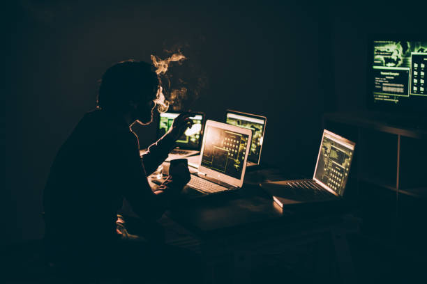 hacker smoking in dark - laptop digital composite stock photos and pictures