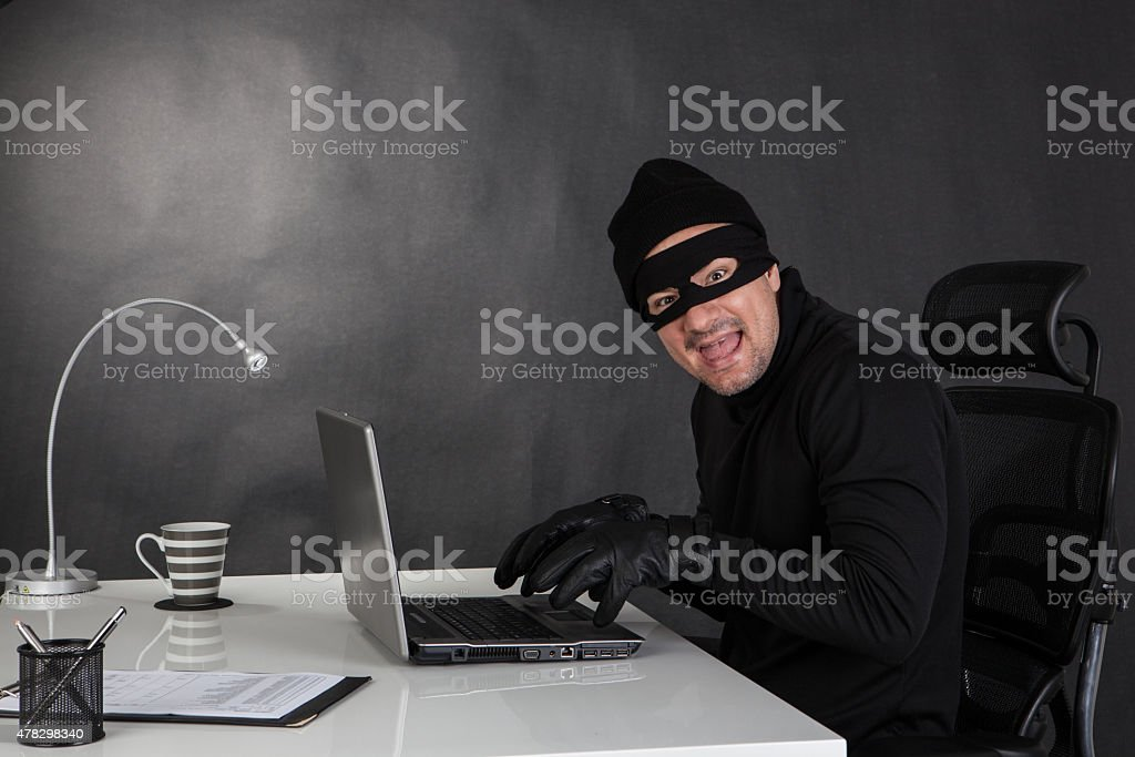 Hacker stealing data and laughing stock photo