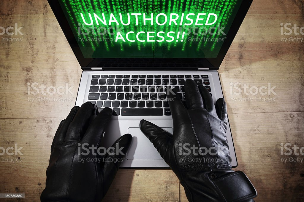 Hacker stealing data from a laptop Computer hacker stealing data from a laptop concept for network security, identity theft, computer crime and unauthorised access 2015 Stock Photo