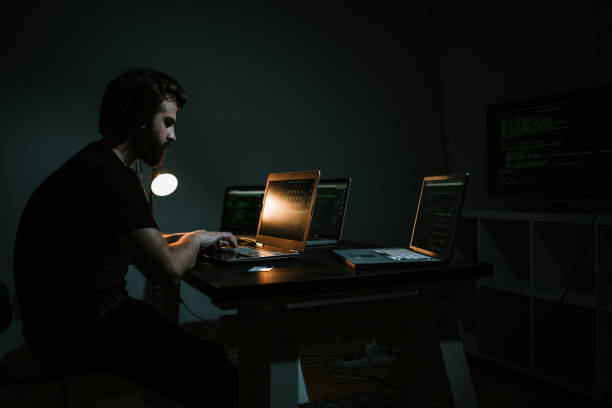 Hacker using computer and stealing data information stock photo