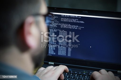 istock Hacker using laptop. Lots of digits on the computer screen 1044168656