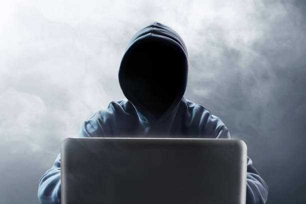 Hacker using laptop stock photo