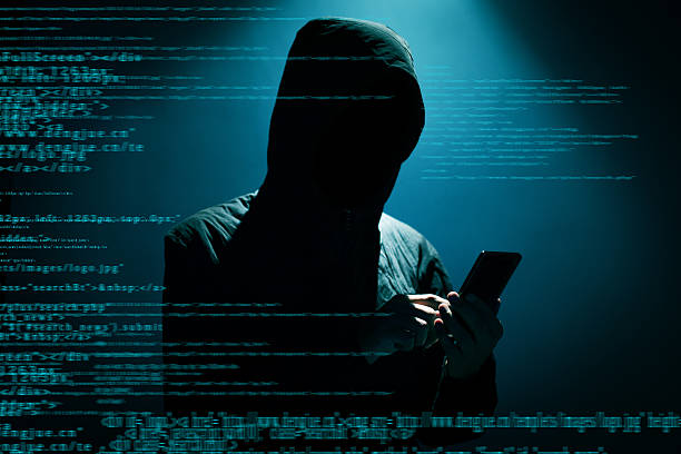 Hacker using phone Hacker Hacker using phone at dark computer crime stock pictures, royalty-free photos & images
