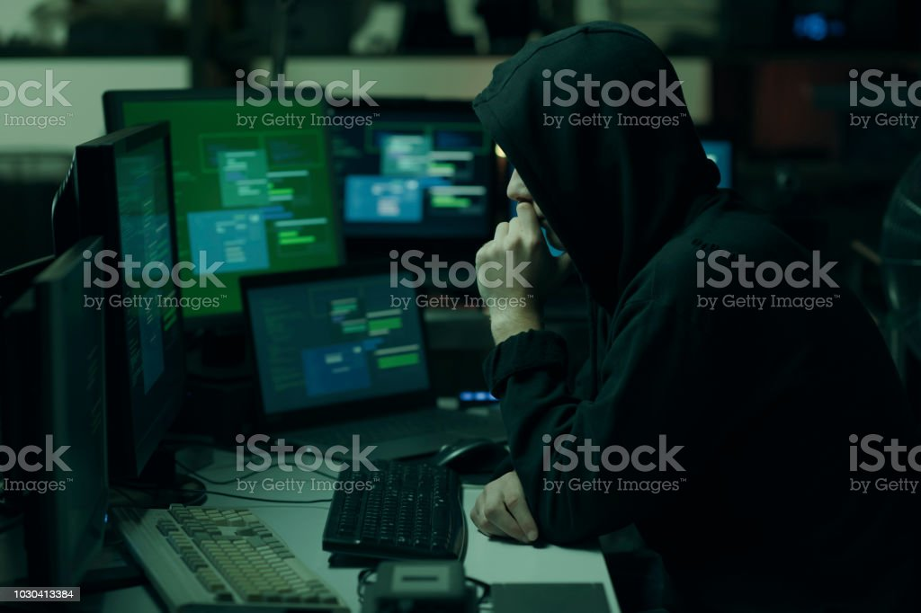Hacker with hoodie working with a computer stock photo