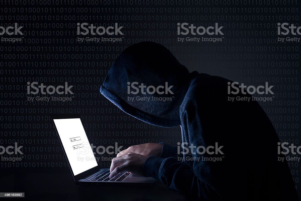 Hacker with laptop initiating cyber attack stock photo