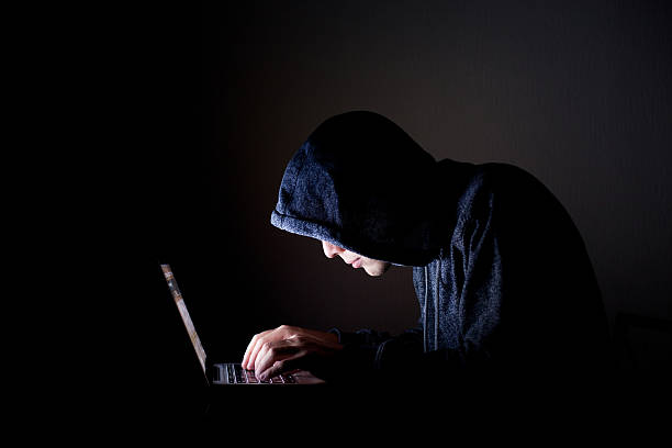hacker with laptop stock photo