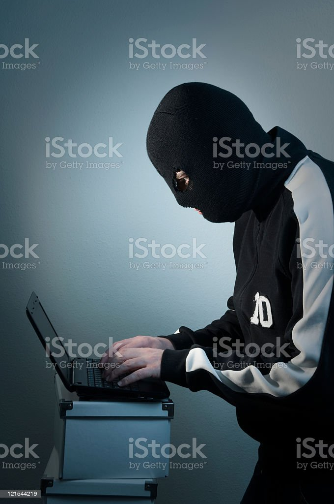 Hacker with mask works on laptop indoor royalty-free stock photo