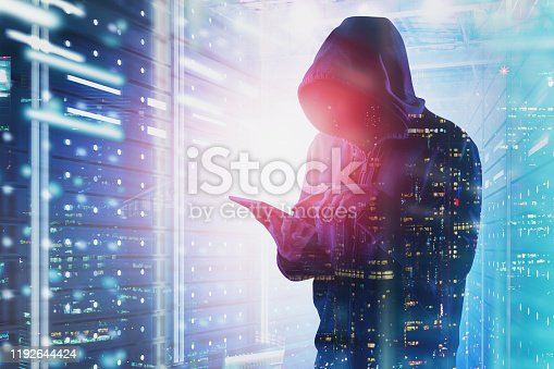 Young hacker with tablet working in data center with double exposure of night city. Concept of identity theft and cybersecurity. Toned image
