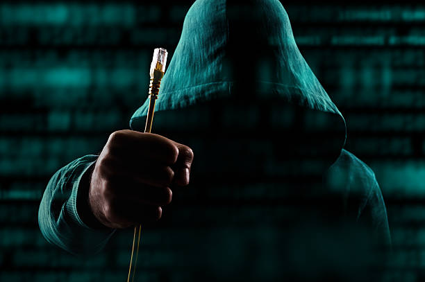 Hacker with unplugged network cable stock photo