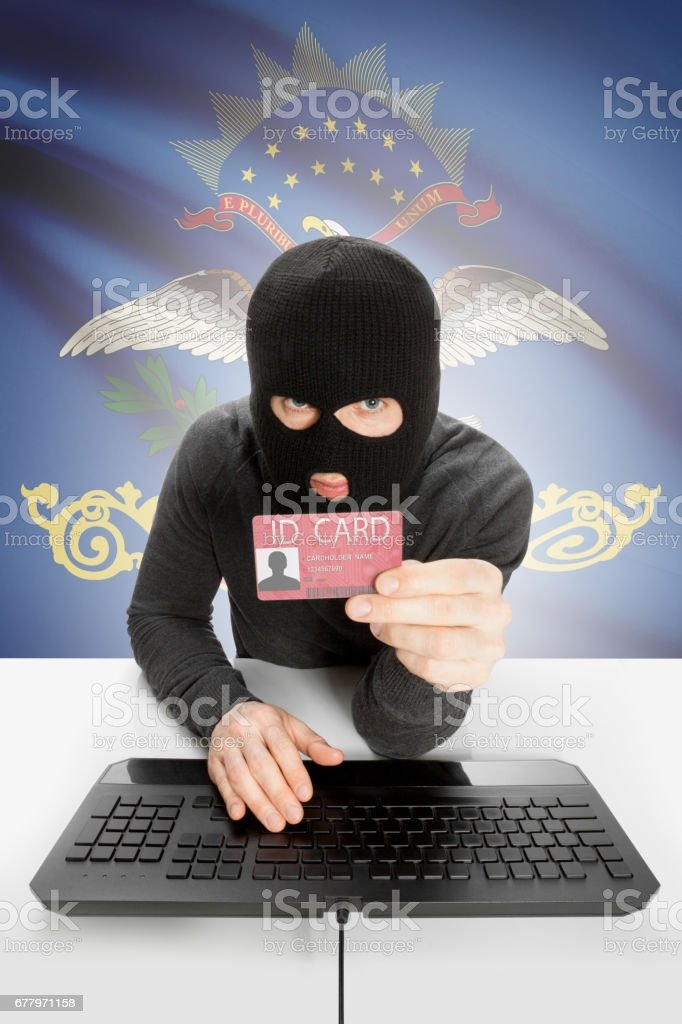 Hacker with USA states flag on background and ID card in hand - North Dakota royalty-free stock photo