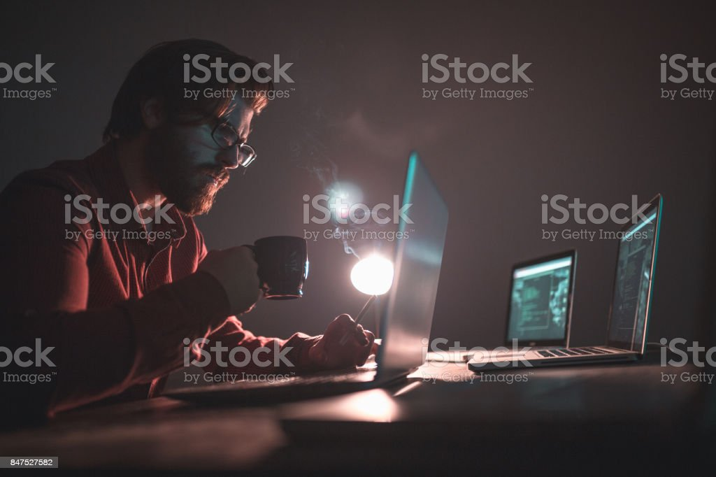 Hacker working on laptop and stealing informations stock photo
