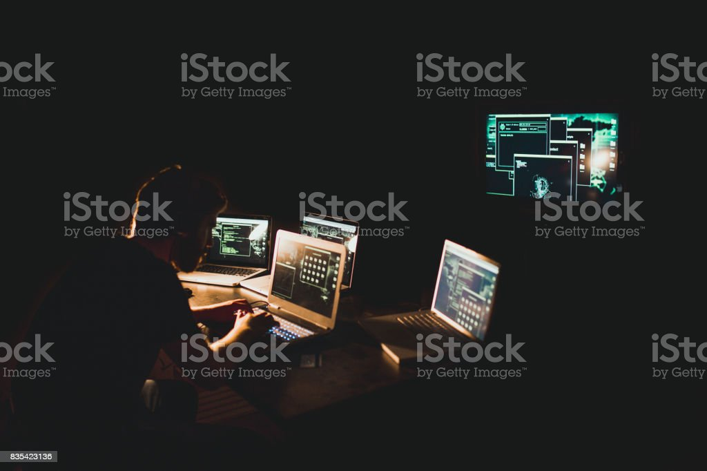 Hacker working on laptop late at night stock photo