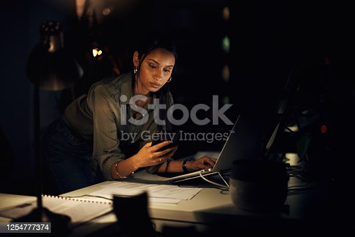 Shot of a young businesswoman using a cellphone while working on a laptop in an office at night