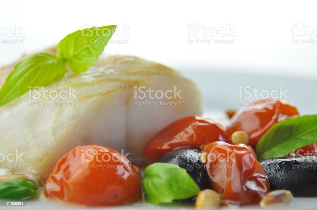 haddock with tomatoes and black olives stock photo