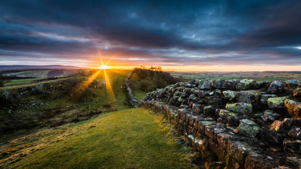 Hadrian's Wall, Northumberland Hadrian's Wall on Walltown Crags at sunset with dramatic clouds. northeastern england stock pictures, royalty-free photos & images