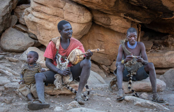 Hadza men resting and singing traditional songs stock photo