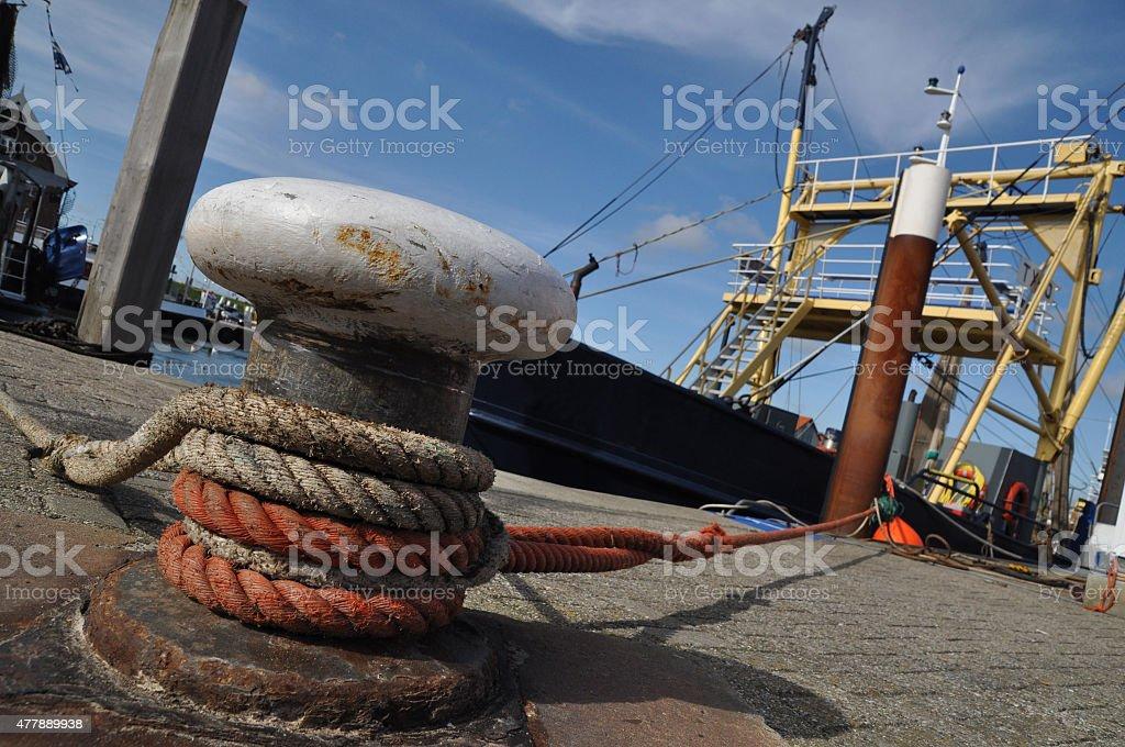 Hafenpoller mit Schiffstau und Fischkutter stock photo