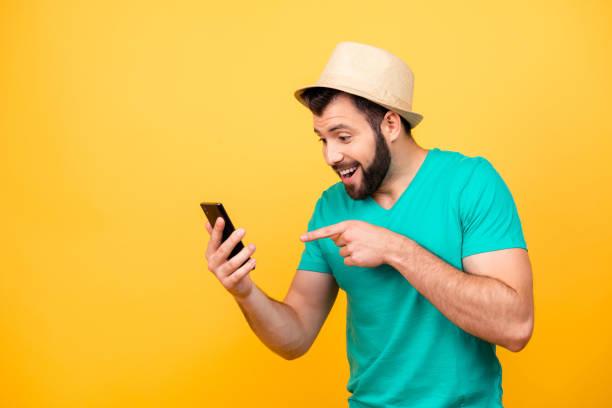 ha-ha! so lustig! porträt von glücklich aufgeregt verrückter mann mit stoppeln trägt hut und grüne tshirt, er zeigt auf seinem smartphone und jubel - lustige texte stock-fotos und bilder