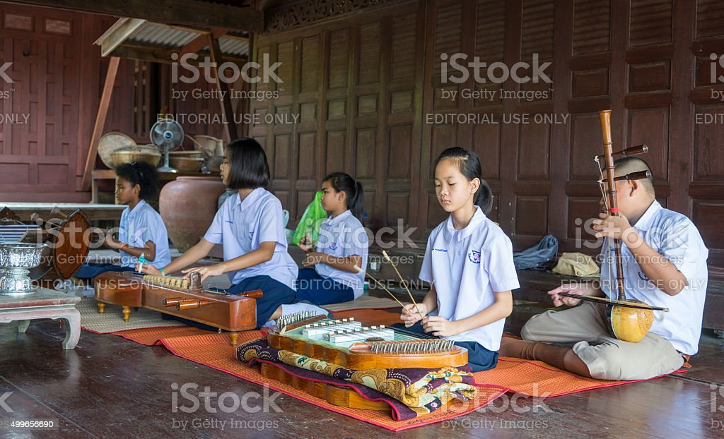 hai Students are performing Thai traditional music in Samchuk Market. stock photo
