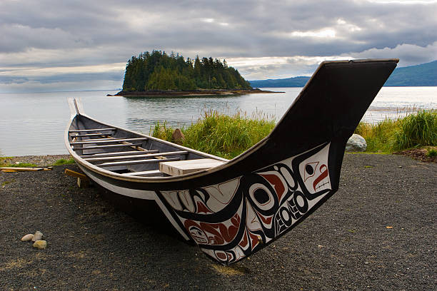 Haida Boat on the shoreline of Haida Gwaii A canoe rests on the shoreline in Haida Gwaii. vancouver island stock pictures, royalty-free photos & images