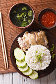 Hainanese chicken rice, chilli sauce and bouillon on the table close-up. vertical view from above