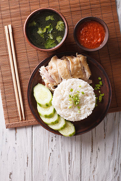 Hainanese chicken rice, chilli sauce and bouillon. vertical top view stock photo