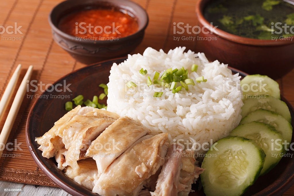 Hainanese chicken rice close-up on a table and broth. horizontal stock photo