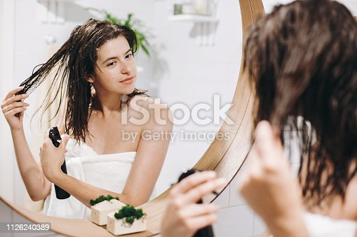 Hair and body care. Young happy woman in white towel applying conditioner mask on hair in bathroom, mirror reflection. Slim sexy woman with natural skin enjoying spa and wellness, relaxing