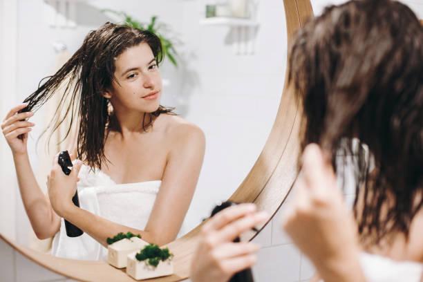 haar- und körperpflege. glückliche mädchen in weißen tuch auftragen conditioner maske auf haare im bad, spiegeln reflexion. schlanke sexy frau mit naturfell spa und wellness genießen, relaxen - feminine badezimmer stock-fotos und bilder