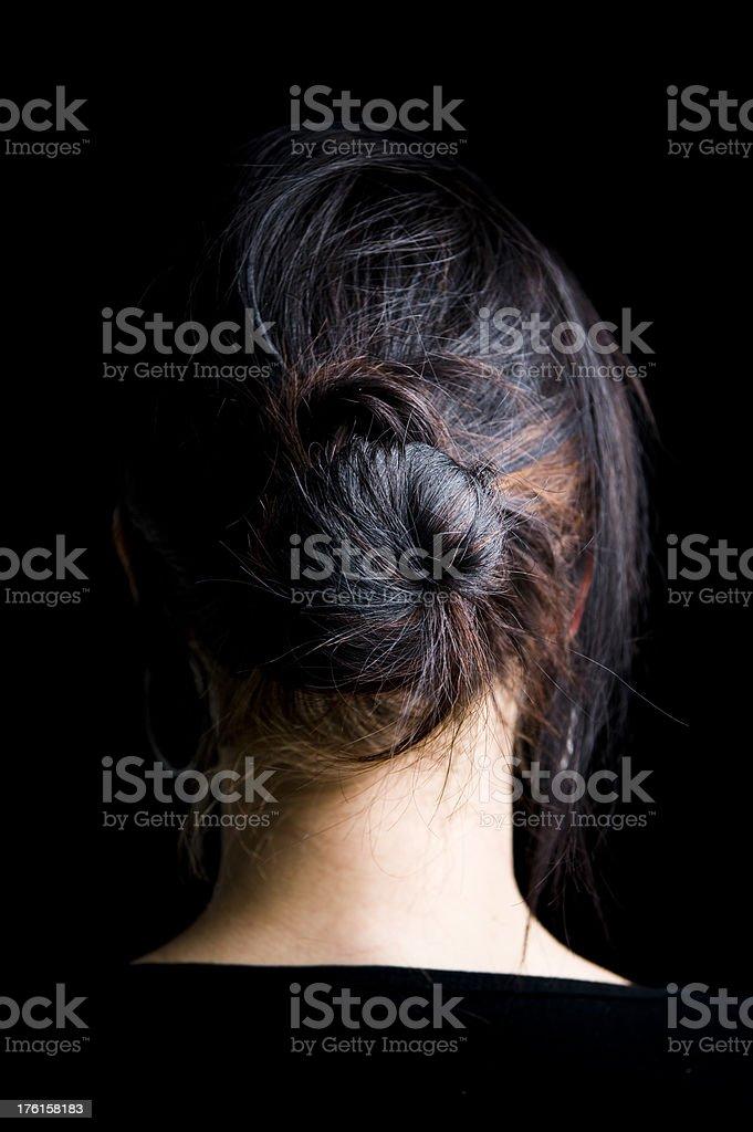 Hair Back of head woman facing away tied in bun. stock photo