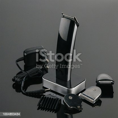 istock Hair Barber Clippers, Haircut accessories on the grey mirror background 1004853434