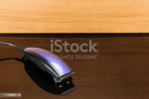 1147090180istockphoto Hair barber clippers, haircut on woody mirror background with copy space 1170308110