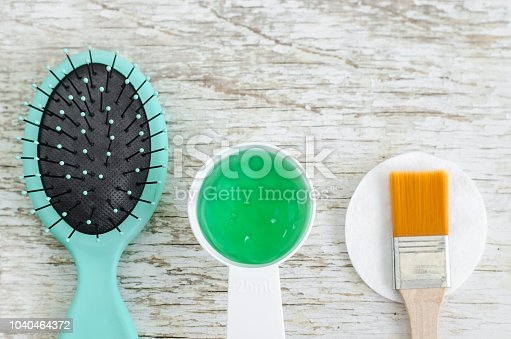 istock Hair brush and small scoop with green gel hair mask (conditioner) with spirulina, aloe vera and marine collagen extracts. Spa and natural skin and hair care concept. Top view, copy space. 1040464372