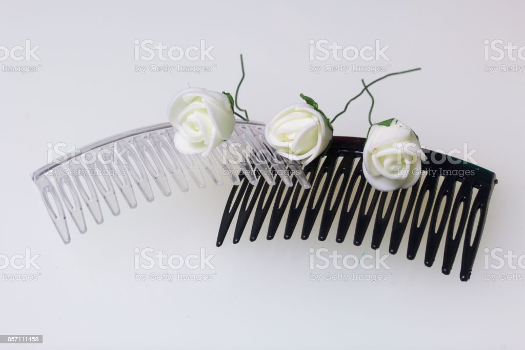 Hair care. Accessories and decorations. Two scallops for hair are transparent and black in color. Artificial rose flowers are beige for interweaving or decorating. On a white background. stock photo