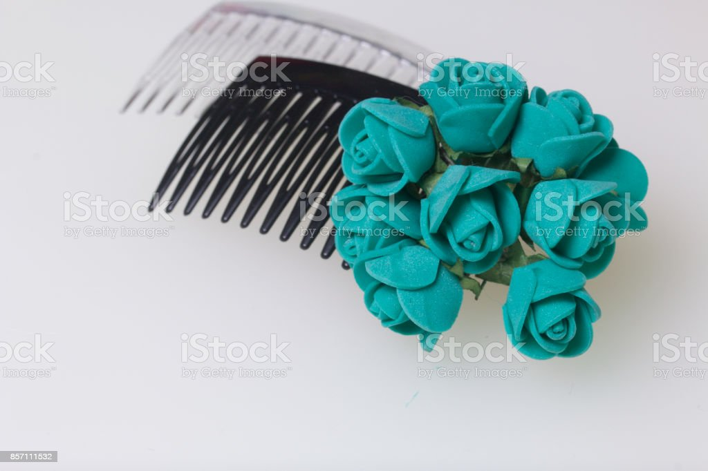 Hair care. Accessories and decorations. Two scallops for hair are transparent and black in color. Artificial rose flowers are emerald for interweaving or decorating. On a white background. stock photo