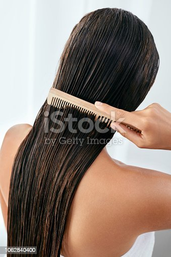 886414246istockphoto Hair Care. Beautiful Woman Brushing Wet Long Hair After Bath 1062840400