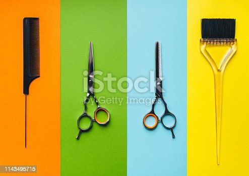696318954 istock photo Hair care. Four tools hairdresser on the background of pastel paper in the form of multi-colored stripes. Minimalist pop art concept. 1143495715