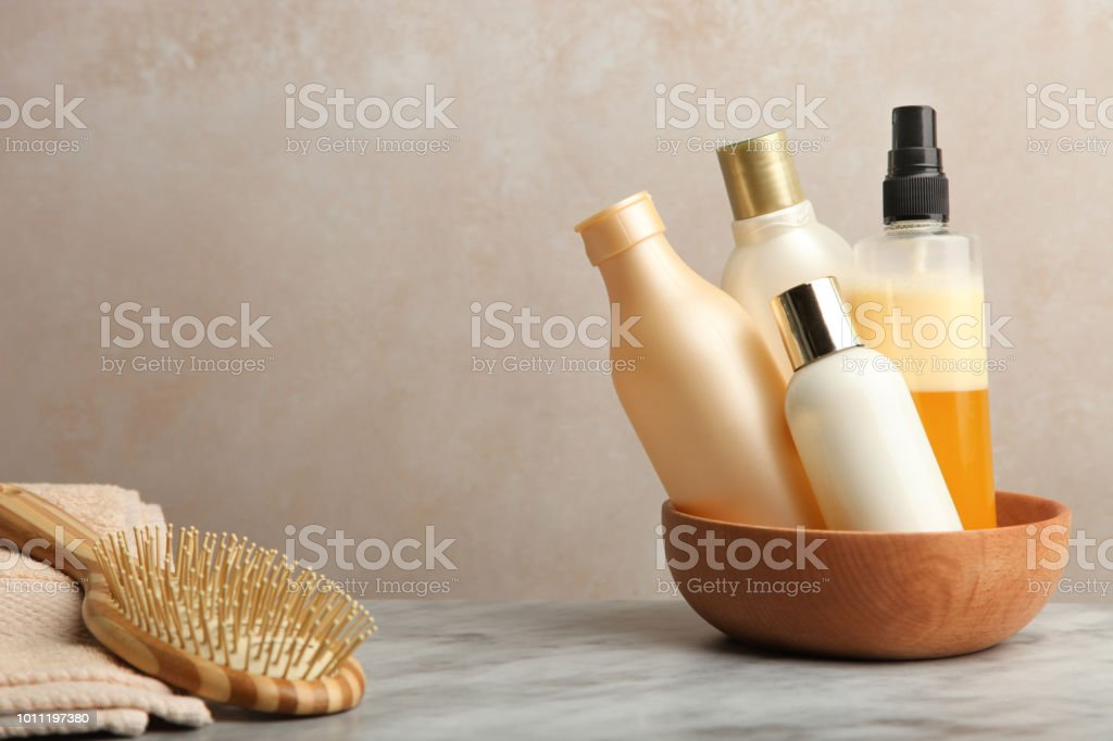 Hair care products on marble table on neutral background.