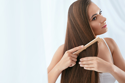 istock Hair Care. Woman Combing Beautiful Long Hair With Wooden Brush 1062840478